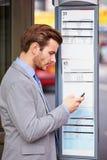 Uomo d'affari At Bus Stop con l'orario della lettura del telefono cellulare immagine stock