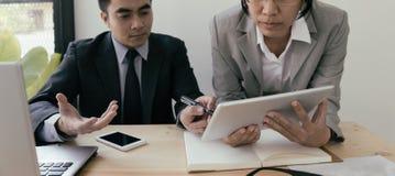 Uomo d'affari And Businesswoman che per mezzo di una compressa digitale per discutere Fotografia Stock