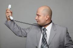 Uomo d'affari calvo con il microtelefono immagini stock