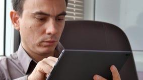Uomo d'affari in camicia facendo uso della compressa digitale moderna stock footage