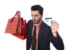 Uomo d'affari in cappello di Santa Claus Christmas che tiene le borse fradicie e la carta di credito in preoccupato in e sforzo Fotografia Stock Libera da Diritti