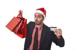 Uomo d'affari in cappello di Santa Claus Christmas che tiene le borse fradicie e la carta di credito in preoccupato in e sforzo Immagini Stock