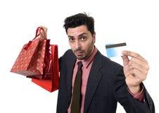 Uomo d'affari in cappello di Santa Claus Christmas che tiene le borse fradicie e la carta di credito in preoccupato in e sforzo Fotografie Stock Libere da Diritti