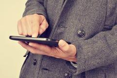 Uomo d'affari in cappotto facendo uso di una compressa, con un effetto del filtro Fotografia Stock