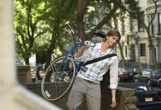 Uomo d'affari Carrying Bicycle Outdoors Immagine Stock