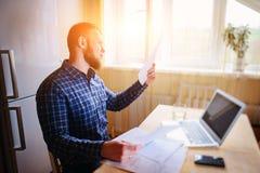 Uomo d'affari a casa, sta lavorando con un computer portatile, controllando il lavoro di ufficio e le fatture Immagini Stock Libere da Diritti