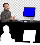 Uomo d'affari casuale che sorride e che parla alla macchina fotografica che mostra qualcosa sul monitor del computer, Alpha Chann immagine stock libera da diritti