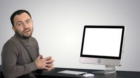 Uomo d'affari casuale che sorride e che parla alla macchina fotografica che mostra qualcosa sul monitor del computer sul fondo di fotografia stock libera da diritti