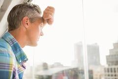 Uomo d'affari casuale disturbato che pende contro la finestra fotografie stock libere da diritti