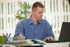Uomo d'affari casuale in ufficio mentre scrivendo sul computer portatile Fotografie Stock