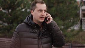 Uomo d'affari caucasico di mezza età che parla sull'autunno del telefono stock footage