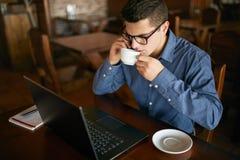 Uomo d'affari caucasico facendo uso del telefono mentre lavorando al computer portatile e giudicando tazza di caffè disponibila C immagini stock