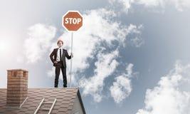 Uomo d'affari caucasico sul segnale stradale di arresto di rappresentazione del tetto della casa con mattoni a vista Immagine Stock Libera da Diritti