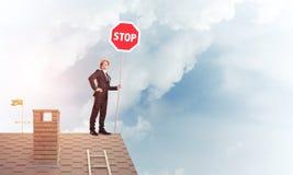 Uomo d'affari caucasico sul segnale stradale di arresto di rappresentazione del tetto della casa con mattoni a vista Immagini Stock
