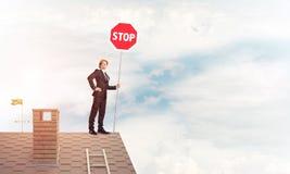 Uomo d'affari caucasico sul segnale stradale di arresto di rappresentazione del tetto della casa con mattoni a vista Fotografia Stock