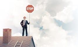 Uomo d'affari caucasico sul segnale stradale di arresto di rappresentazione del tetto della casa con mattoni a vista Fotografia Stock Libera da Diritti
