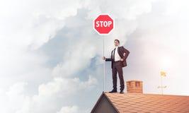 Uomo d'affari caucasico sul segnale stradale di arresto di rappresentazione del tetto della casa con mattoni a vista Immagine Stock