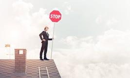 Uomo d'affari caucasico sul segnale stradale di arresto di rappresentazione del tetto della casa con mattoni a vista Fotografie Stock Libere da Diritti