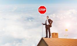 Uomo d'affari caucasico sul segnale stradale di arresto di rappresentazione del tetto della casa con mattoni a vista Media misti Immagine Stock