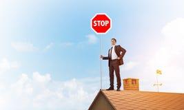 Uomo d'affari caucasico sul segnale stradale di arresto di rappresentazione del tetto della casa con mattoni a vista Media misti Fotografie Stock Libere da Diritti