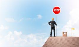 Uomo d'affari caucasico sul segnale stradale di arresto di rappresentazione del tetto della casa con mattoni a vista Media misti Immagini Stock