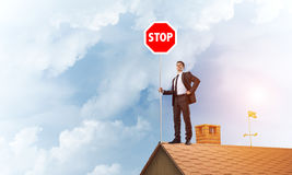 Uomo d'affari caucasico sul segnale stradale di arresto di rappresentazione del tetto della casa con mattoni a vista Media misti Immagine Stock Libera da Diritti