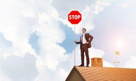 Uomo d'affari caucasico sul segnale stradale di arresto di rappresentazione del tetto della casa con mattoni a vista Media misti Fotografia Stock