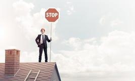 Uomo d'affari caucasico sul segnale stradale di arresto di rappresentazione del tetto della casa con mattoni a vista Immagini Stock Libere da Diritti