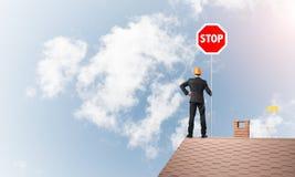 Uomo d'affari caucasico sul segnale stradale di arresto di rappresentazione del tetto della casa con mattoni a vista Media misti Fotografia Stock Libera da Diritti