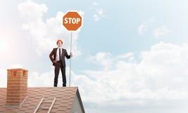 Uomo d'affari caucasico sul segnale stradale di arresto di rappresentazione del tetto della casa con mattoni a vista Media misti Fotografie Stock