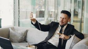 Uomo d'affari caucasico in vestiti convenzionali che sorride e che ha video chiamata online con lo smartphone e che ondeggia feli archivi video