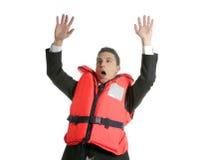 Uomo d'affari che affonda nella crisi, metafora del giubbotto di salvataggio Immagini Stock