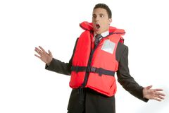 Uomo d'affari che affonda nella crisi, metafora del giubbotto di salvataggio Fotografia Stock
