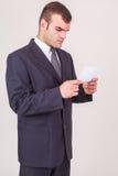 Uomo d'affari che aggrotta le sopracciglia come legge una nota Fotografia Stock Libera da Diritti