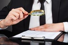 Uomo d'affari che analizza documento con la lente d'ingrandimento allo scrittorio Fotografia Stock