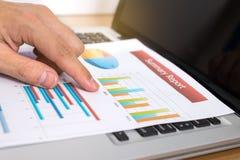 Uomo d'affari che analizza i grafici di investimento con il computer portatile Finanza marzo fotografia stock