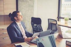 Uomo d'affari che analizza i grafici ed i grafici di reddito Immagini Stock