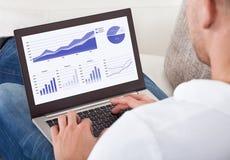 Uomo d'affari che analizza i grafici sul suo computer portatile fotografie stock
