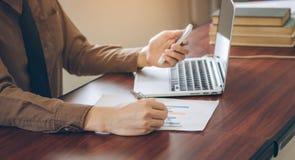 Uomo d'affari che analizza il documento del grafico con il computer portatile e che utilizza telefono cellulare nell'ufficio Immagine Stock