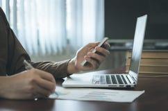 Uomo d'affari che analizza il documento del grafico con il computer portatile e che utilizza telefono cellulare nell'ufficio Immagini Stock