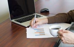 Uomo d'affari che analizza il documento del grafico e che tiene caffè in ufficio Fotografia Stock Libera da Diritti