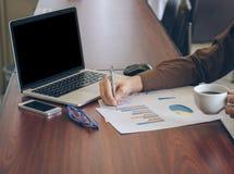 Uomo d'affari che analizza il documento del grafico e che tiene caffè in ufficio Immagini Stock Libere da Diritti