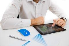 Uomo d'affari che analizza le statistiche finanziarie visualizzate sullo schermo della compressa Fotografia Stock Libera da Diritti