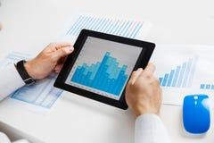 Uomo d'affari che analizza le statistiche finanziarie visualizzate sullo schermo della compressa Immagini Stock
