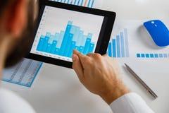 Uomo d'affari che analizza le statistiche finanziarie visualizzate sullo schermo della compressa Immagine Stock
