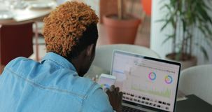 Uomo d'affari che analizza risultato di lavoro il suo gruppo, guardando i grafici ed i grafici su un monitor del computer portati stock footage