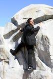 Uomo d'affari che arrampica una roccia Immagini Stock