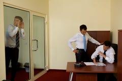Uomo d'affari che ascolta di nascosto sulla conversazione fra i colleghi in ufficio Immagini Stock Libere da Diritti