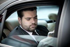 Uomo d'affari che ascolta la musica sul suo telefono Fotografie Stock Libere da Diritti