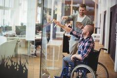 Uomo d'affari che assiste il collega di handicap in ufficio creativo fotografia stock libera da diritti